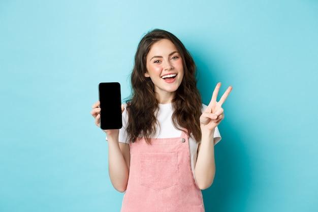 Leuke jonge vrouw die lacht en v-teken toont met een leeg smartphonescherm, app of mobiele winkel demonstreert, staande tegen een blauwe achtergrond.