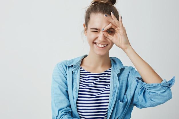 Leuke jonge vrouw die monocle gebaar maakt en door vingers kijkt