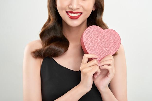 Leuke jonge vrouw die roze hartsymbool houdt tegen bleke witte achtergrond