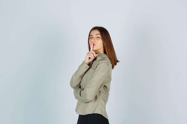 Leuke jonge vrouw die stiltegebaar in overhemd, rok toont en er verstandig uitziet.