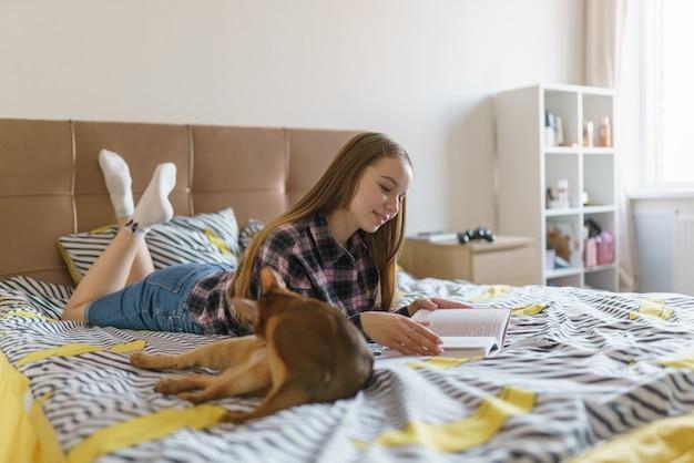 Leuke jonge vrouw die thuis in het weekend een boek leest.