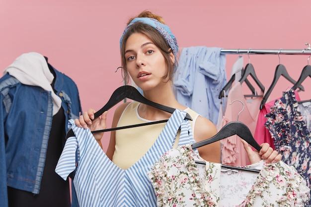 Leuke jonge vrouw die twee verschillende zomerjurken houdt die beslissen welke meer geschikt is om te dragen tijdens een wandeling. mensen, kleding, stijl en mode
