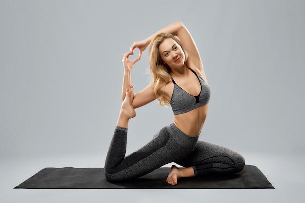Leuke jonge vrouw die yoga doet met een goed humeur
