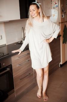 Leuke jonge vrouw die zich dichtbij bureau in de keuken bevindt. lachende langharige huisvrouw.