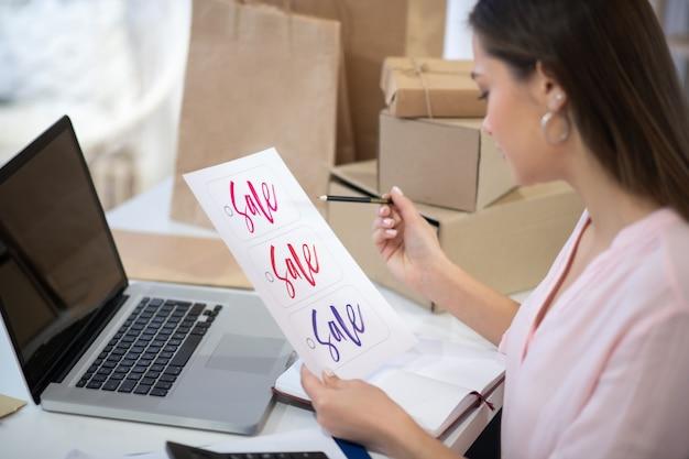 Leuke jonge vrouw die zich voorbereidt op de verkoop tijdens het runnen van haar online winkel