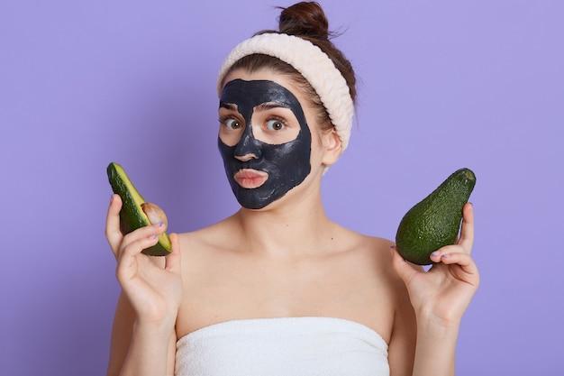 Leuke jonge vrouw gewikkeld in een handdoek direct kijken naar de camera, met de helft van verse rijpe avocado