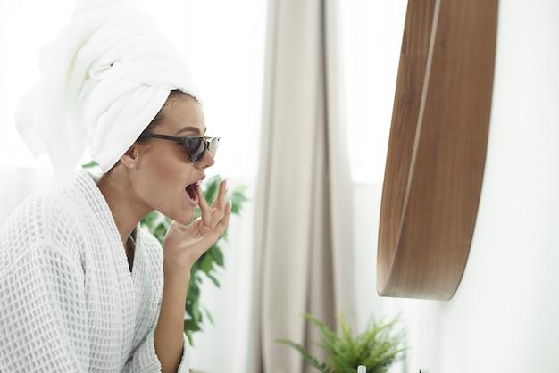 Leuke jonge vrouw in een badjas, met zwarte zonnebril die voor de badkamerspiegel voor de gek houdt.