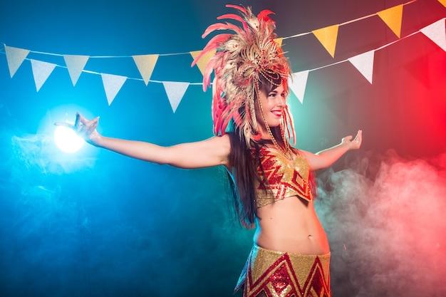 Leuke jonge vrouw in helder kleurrijk carnaval-kostuum