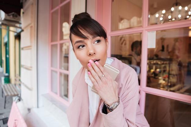 Leuke jonge vrouw in roze jasje heeft betrekking op haar mond met palm