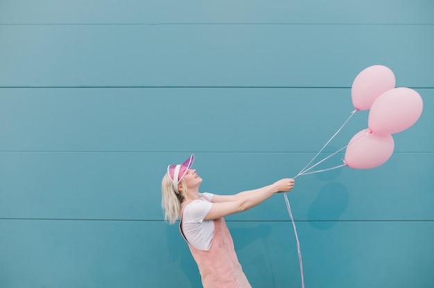 Leuke jonge vrouw in roze kleren die zich met ballons bevinden