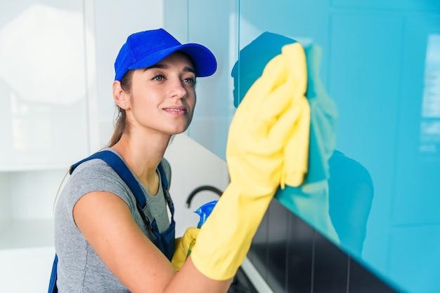 Leuke jonge vrouw in werkkleding en beschermende rubberen gele handschoenen schoonmaken van het meubilair in moderne hi-tech keuken.