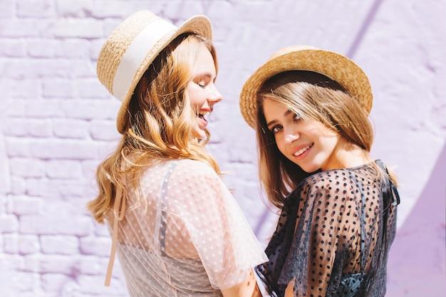 Leuke jonge vrouw in zwarte jurk met naakt make-up op zoek met interesse, terwijl haar vriend in witte kleding gelukkig lachen