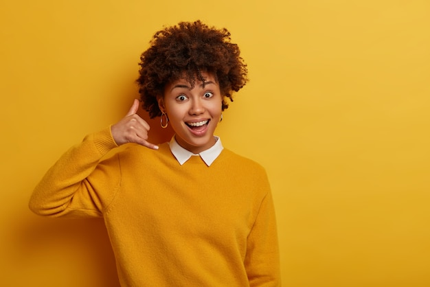 Leuke jonge vrouw maakt telefoongebaar, shows bel me terug teken