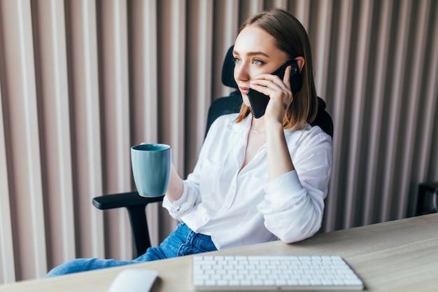 Leuke jonge vrouw met aan de telefoon tijdens het werken op een laptopcomputer aan het bureau naast een koffiekopje