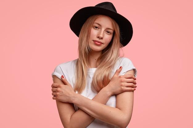 Leuke jonge vrouw met een aantrekkelijke uitstraling, houdt de handen gekruist, gekleed in een casual t-shirt en zwarte hoed, ziet er serieus uit