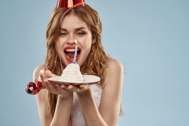 Leuke jonge vrouw met een cupcake en kaarsen viert verjaardag, studio, blauwe muur