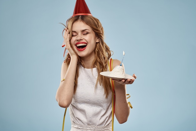 Leuke jonge vrouw met een cupcake en kaarsen viert verjaardag
