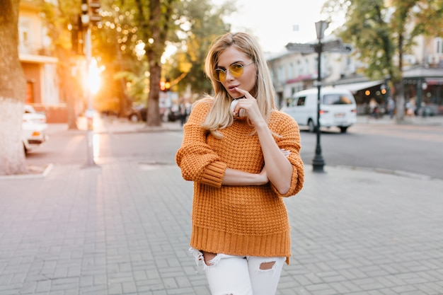 Leuke jonge vrouw met glanzend blond haar poseren op stadsplein met tevreden gezichtsuitdrukking