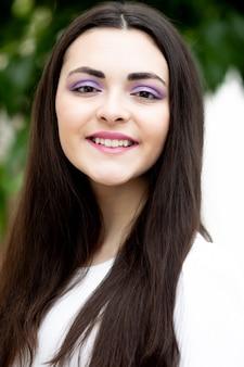 Leuke jonge vrouw met paarse oogschaduw buiten