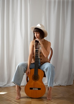Leuke jonge vrouw poseren met een gitaar binnenshuis