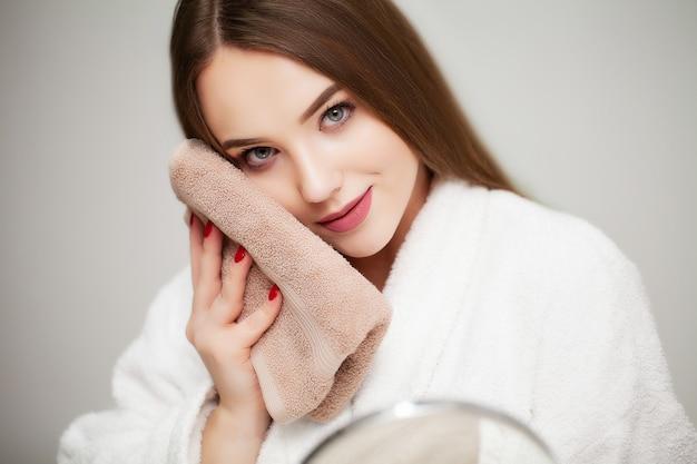 Leuke jonge vrouw veegt het gezicht handdoek na het douchen af