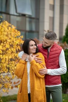 Leuke jonge vrouw wordt geknuffeld door haar vriendje terwijl ze zich door hem geliefd voelt