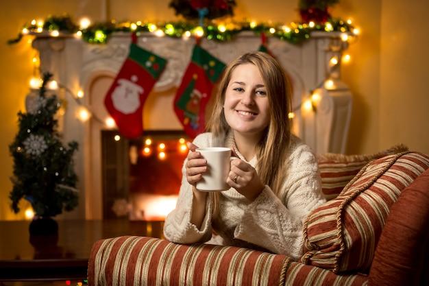 Leuke jonge vrouw zit bij de open haard met een kopje thee met kerstmis