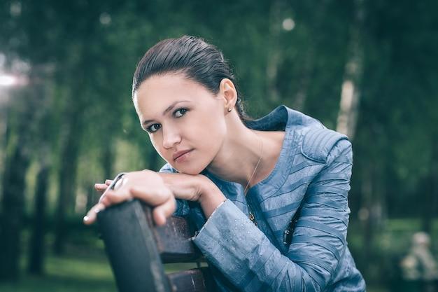Leuke jonge vrouw zittend op een bankje in het park