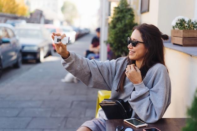 Leuke, jonge vrouwelijke blogger die zich voordeed op camera.