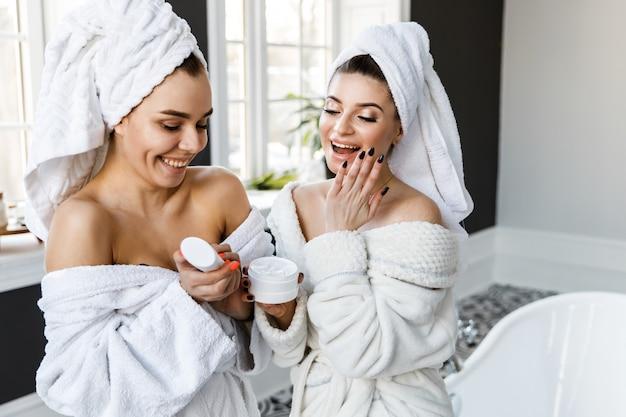 Leuke jonge vrouwen gekleed in witte badjassen en handdoeken op het hoofd hebben plezier in de badkamer