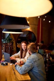 Leuke jonge zakenvrouw en zakenman in gezellig café. freelance en werken op afstand