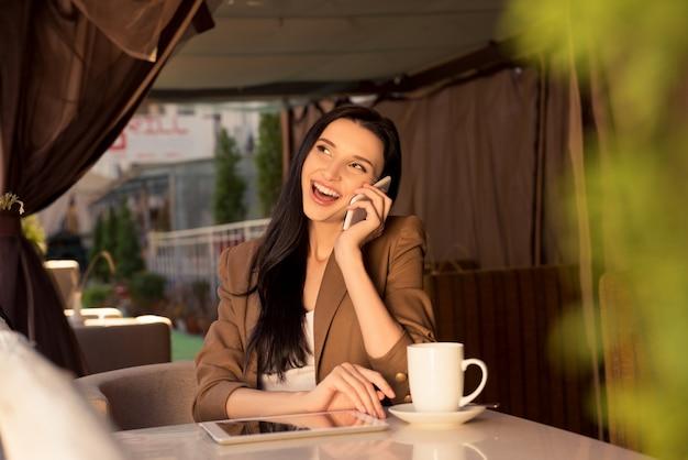 Leuke jonge zakenvrouw in een café praten aan de telefoon