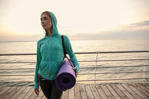 Leuke jongedame die aan zee loopt, yoga gaat beoefenen en zich 's ochtends uitrekt, een paarse yogamat vasthoudt en wegkijkt.