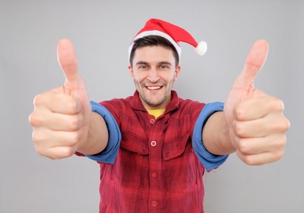 Leuke jongeman met kerstman hoed