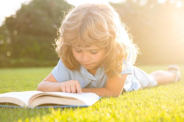 Leuke jongen die een boek leest dat op gras legt. kind dat een boek leest in het zomerpark.