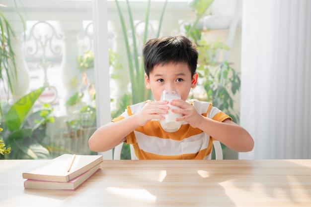 Leuke jongen die een glas melk drinkt die aan een tafel zit na het huiswerk te hebben gemaakt