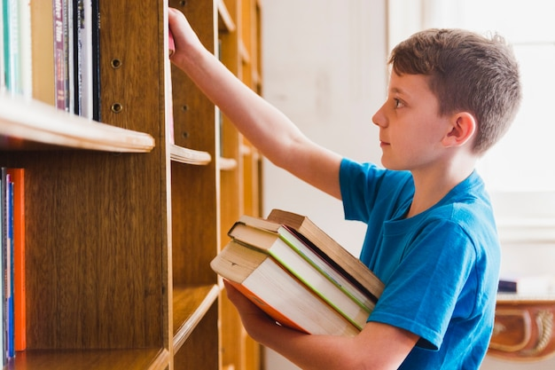 Leuke jongen die gekozen boeken van de plank neemt