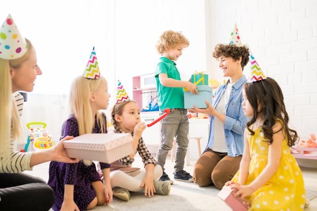 Leuke jongen die giftdozen geeft aan moeder bij verjaardagspartij