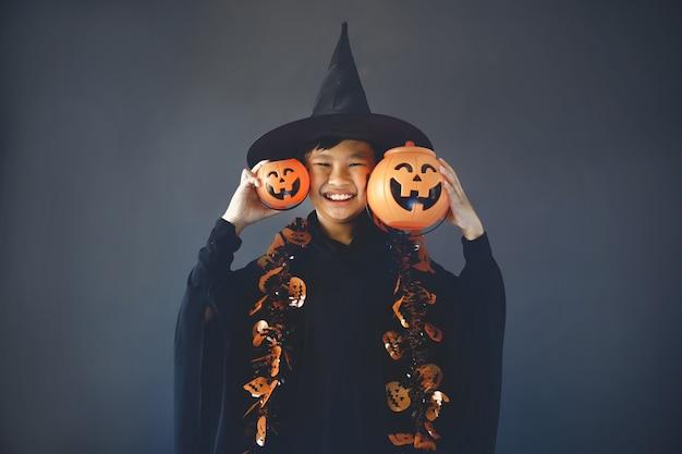 Leuke jongen die halloween viert door een heksenkostuum te dragen en halloween-decoratieaccessoires vast te houden