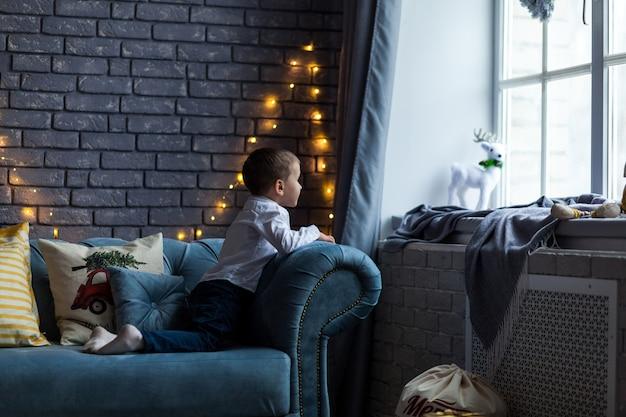 Leuke jongen die het venster in kerstmistijd bekijkt