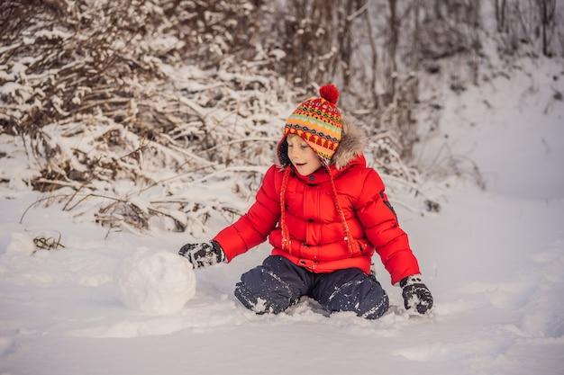 Leuke jongen die in rode de winterkleren een sneeuwman bouwt