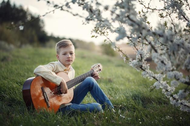 Leuke jongen die muziek maakt die de gitaar op aard speelt.