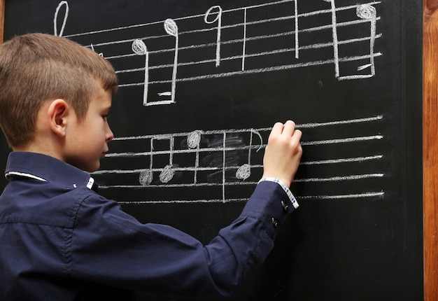 Leuke jongen die op het bord met muzieknoten schrijft, in de klas
