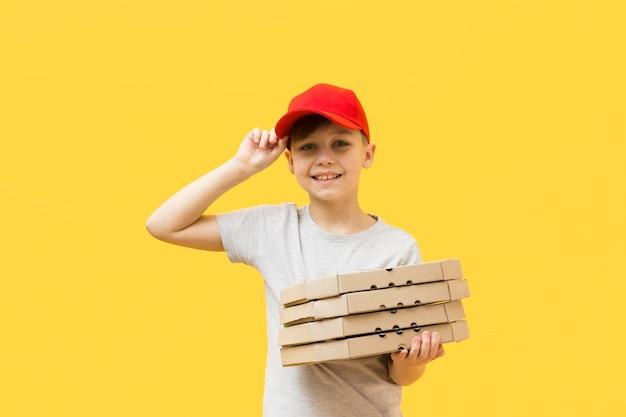 Leuke jongen die pizzadozen houdt