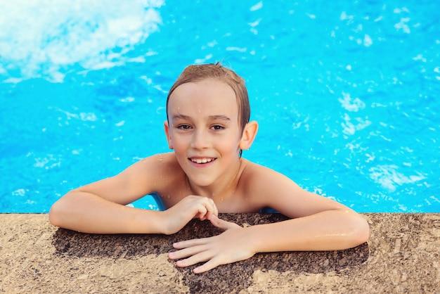 Leuke jongen die plezier heeft in het zwembad. gelukkig kind zwemmen in het buitenzwembad. zomer vakantie concept. waterspelletjes en waterpret voor kinderen.
