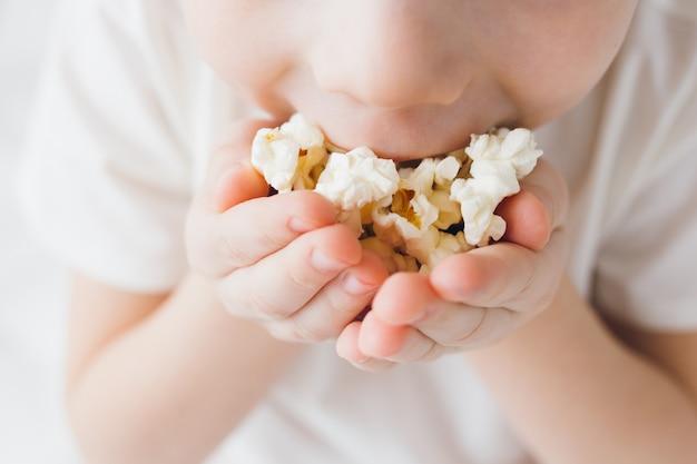 Leuke jongen die popcornzitting in bed met wit linnen eet