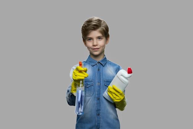 Leuke jongen die schoonmaakproducten houdt. knap jong geitje dat in rubberhandschoenen fles met wasmiddel houdt. home desinfectie. lente schoonmaak concept.