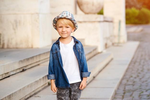 Leuke jongen die stijlvolle zomeroutfit draagt. kind met positieve emoties. zomermode voor kinderen.