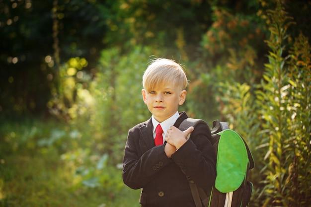 Leuke jongen die terug naar school gaat. jongen in het pak. kind met rugzak op de eerste schooldag