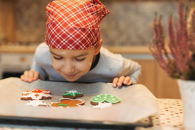 Leuke jongen die van smaak van vers gesteunde kerstmiskoekjes geniet.